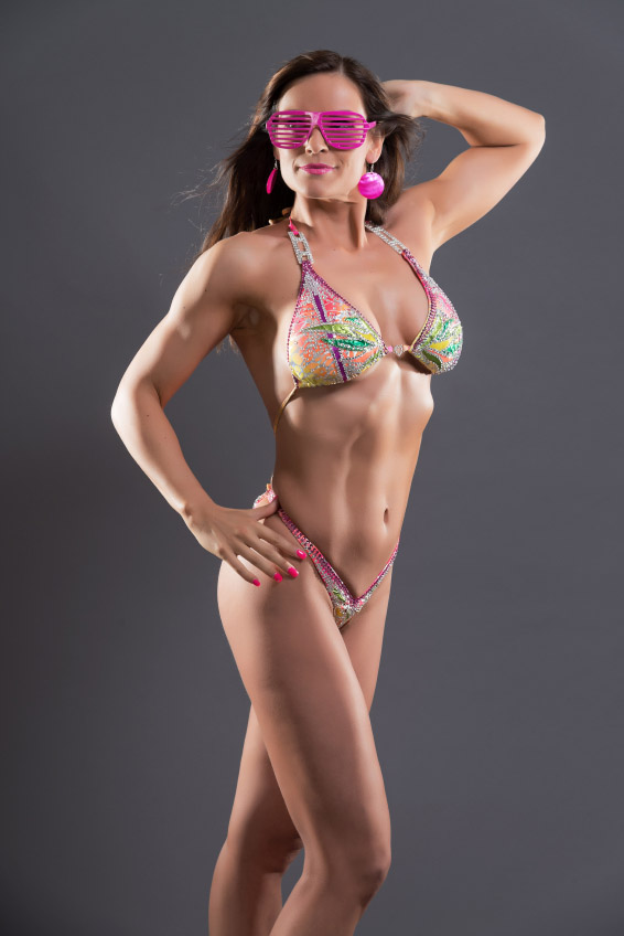 Muscled fitness woman wearing bikini and retro 80s pink sunglasses. Brown hair. Studio shot against grey.