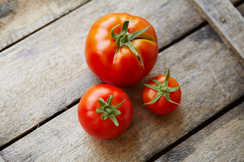 Ripe tomatoes on a wooden table. Shallow depth of field